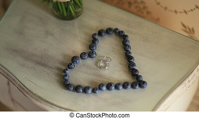 Wedding rings in a heart of a blueberry on a table