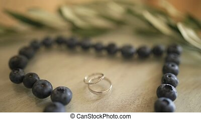 Wedding rings in a heart of a blueberry on a table.
