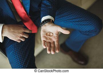 Wedding rings in hands of the groom.