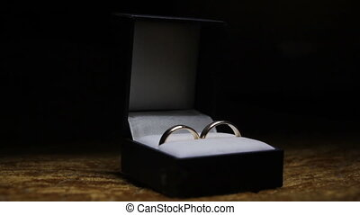 Wedding rings in red black box on dark background with moving light