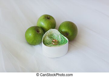 wedding rings in the cassette near green apples