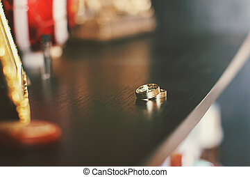 Wedding rings lie and sparkle on a dressing table