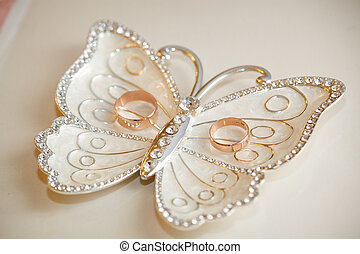 Wedding rings lie on a plateau in the form of a butterfly. ...