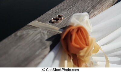 wedding rings lie on a wooden bridge