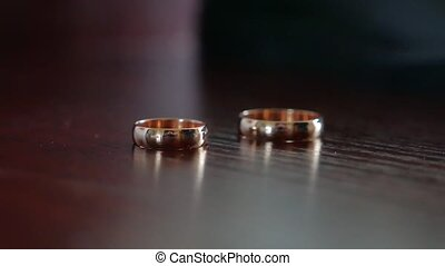 Wedding rings lie on a wooden table. wedding day love -...