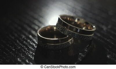 Wedding rings lie on the black table
