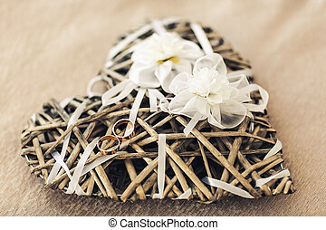 Wedding rings lie on the decorative heart of the vine, decorated with artificial flowers.