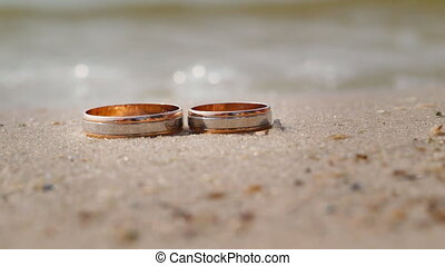 Wedding rings lying on the sand against the background of the surf