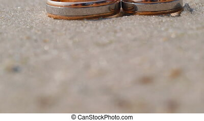 Wedding rings lying on the sand against the background of...