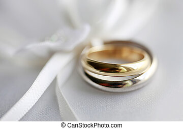 Wedding rings on a blue satiny fabric. Depth of field