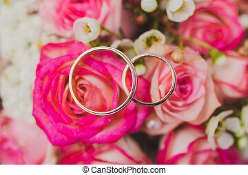 Wedding rings on a bouquet of pink, red flowers