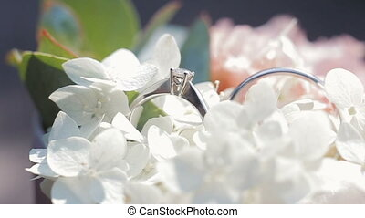 Wedding rings on a bouquet of white flowers. Close up. Rotating composition of Wedding rings and bouquet of white and pink flowers with green leaves.
