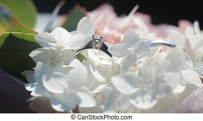 Wedding rings on a bouquet of white flowers. Rotating composition of Wedding rings and bouquet of white and pink flowers with green leaves. Close up.