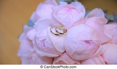 Wedding rings on a bouquet of white flowers. wedding rings...