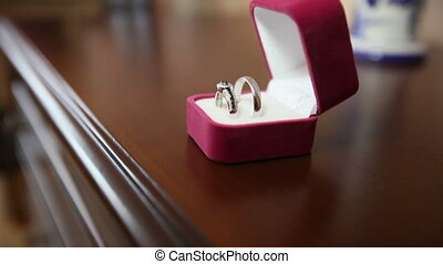 Wedding rings on a wooden table in a box