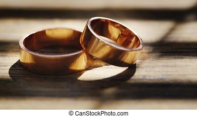 Wedding rings on a wooden texture