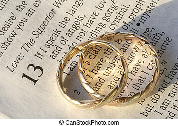 Wedding rings on bible Pair of wedding rings and a red rose
