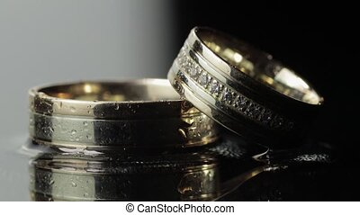 Wedding rings on black and white water surface shining with light. Close up