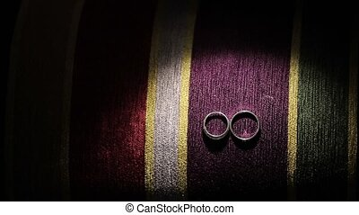 Wedding rings on colourful background with light