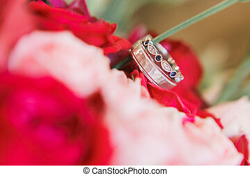 wedding rings on flowers bouquet. Close-up view.