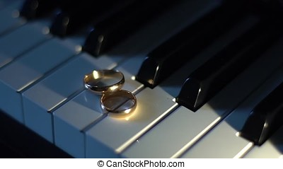 Wedding rings on piano keys. Point source of light.