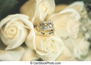 Wedding rings on soft blurred roses background