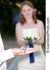 wedding rings on the grooms palm with the bride smiling and holding flowers in the background