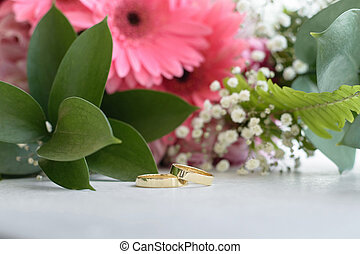 Wedding rings on the table, on the background of a bouquet of flowers