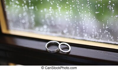 Wedding rings on the window in the rain. Drops on the glass.