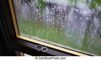 Wedding rings on the window in the rain. Drops on the glass. Tes