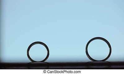 Wedding rings - one rolls to another on blue background