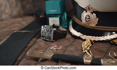Wedding rings, perfume and seaman hat on table. Expensive watch and belt. Sailor themed ceremony. Marine dagger. Concept marriage, masculine, decoration. Sea engagement