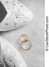 wedding rings - two gold wedding rings and shoes on white...