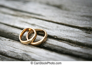 Two wedding rings on top of each other lying on a piece of wood