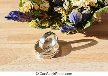 Wedding rings with dry flower on wooden background