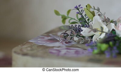 wedding rings with flowers on a table