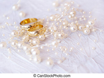 Wedding rings with pearls, soft focus.