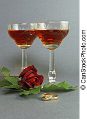 Wedding rings with two glasses of wine.