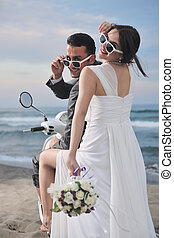 just married couple on the beach ride white scooter
