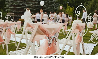 Wedding scenery in the open air. Bouquets of flowers. The invited guests together with the bride and groom are waiting for the festive ceremony.
