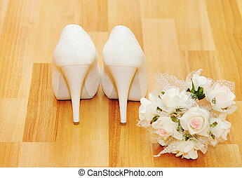 Wedding shoes for the bride and a bunch of flowers