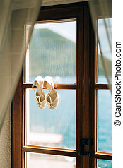 Wedding shoes of the bride at a window.