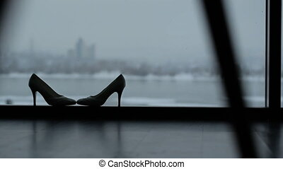 Wedding shoes stand on windowsill in dark room. It is mainly...