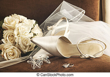Wedding shoes with bouquet of white roses and ring on chair