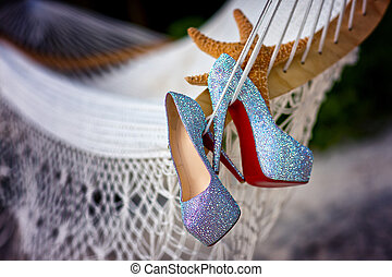 Wedding shoes with diamante near starfish over white grid ...