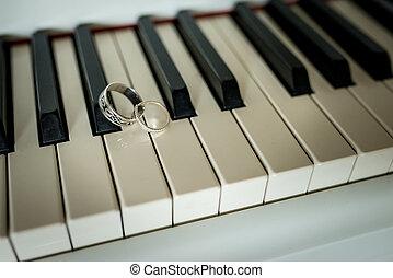 Wedding silver rings lying on the piano keys
