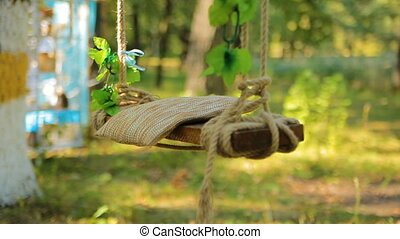 Wedding swing decorated with rope hanging on the branches of the old willow