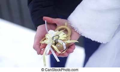 Wedding symbol, lock in hands of bride and groom. Newlyweds fix the lock on the bridge as a symbol of love. Padlock in the hands of the bride and groom. Lock in heart shape on the railing of bridge - a symbol of happy and long married life of bride and groom. Castle sign of eternal light love imprisoned between the bride and groom or husband and wife wonderful tradition contract. Bride and groom makingt the tradition at weddings hanging the lock on the bridge. Love