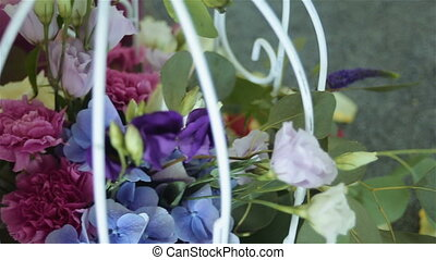 Wedding table decorated with bird's cage, flowers, and pearl...