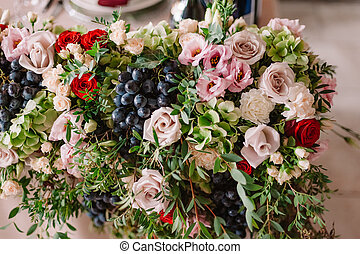 Wedding table decoration with the pink flowers, grape and...
